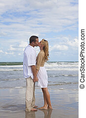Man and Woman Couple Holding Hands Kissing On A Beach - A ...