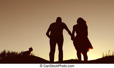 Man and woman couple in love silhouette jumping in slow motion video. Man and woman joy running sunlight and jumping on silhouette nature