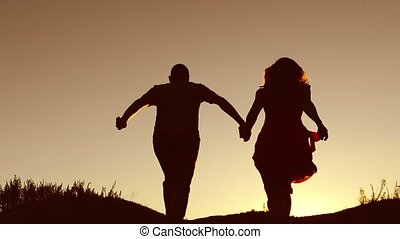 Man and woman couple in love silhouette jumping in slow motion video. Man and woman joy running sunlight and jumping on nature silhouette