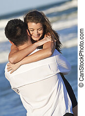 A young man and woman happy having fun and embracing as a romantic couple on a beach