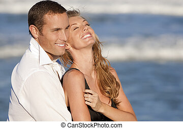 A young man and woman embracing and laughing as a happy romantic couple on a beach
