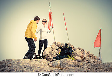 Man and Woman couple Travelers on Mountain summit with backpack Traveling Mountaineering concept fog on background