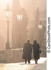 Man and woman couple walk on Charles Bridge in foggy morning, Prague, Czech Republic. Romantic Prague theme