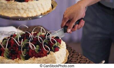 Man and woman cutting celebration cake
