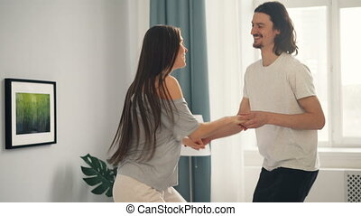 Man and woman dancing on bed in modern apartment having fun together
