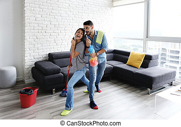 Man And Woman Dancing While Cleaning Home