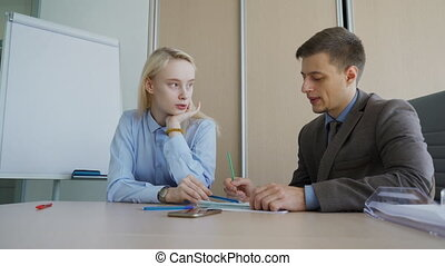 Man and woman discuss working issues,sitting in modern office.