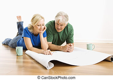 Man and woman discussing blueprints. - Middle-aged couple...