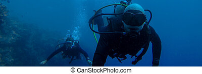 Man and Woman diving in the deep blue sea