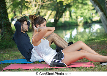man and woman doing abs outside