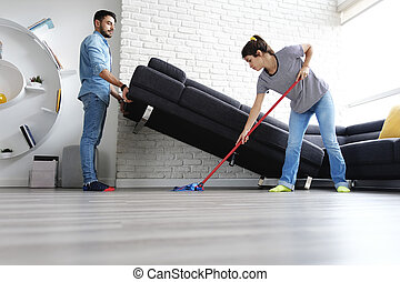 Man And Woman Doing Chores Cleaning Floor