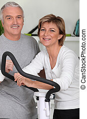 Man and woman doing cross trainer