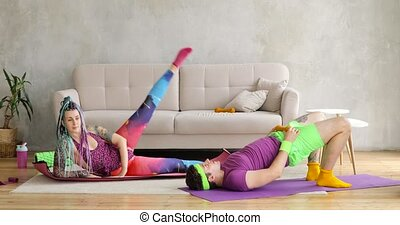 Man and woman doing fitness exercises on mats together in living room at home.