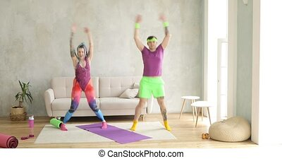 Man and woman doing jumping aerobic fitness exercises at home in living room.