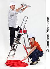 Man and woman doing plumbing work