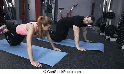 Man and woman doing pushups in a gym