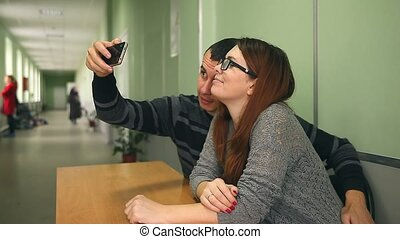 man and woman doing self on the smartphone sitting at a table in the hallway
