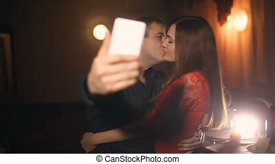 man and woman doing selfie smartphone on the evening in a cafe romantic love   lifestyle