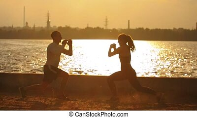 Man and woman doing warm-up before the training on the...
