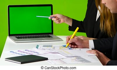 Man and woman draw a graph. Work with green screen monitor in the office