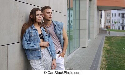 Man and woman dressed in casual street style pose before a...