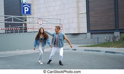 Man and woman dressed in casual street style run on the ...