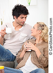 Man and woman drinking coffee on a couch