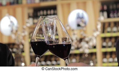 Man and woman drinking red wine. Close-up hands with glasses. Close up of hands of young loving couple clinking glasses of red wine