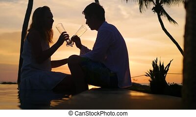 man and woman drinking wine on the beach sunset.Romantic evening for two