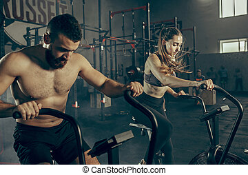 Man and woman during exercises in the fitness gym. Cross Fit.