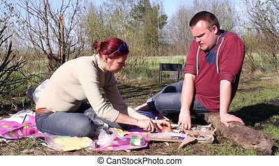 Man and woman eat kebabs outdoors