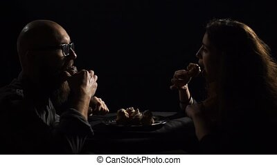 man and woman eating eclairs on black background, looking at each other