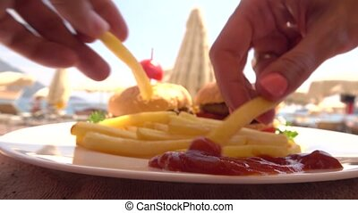 Man and woman eating french fries with ketchup on the beach...