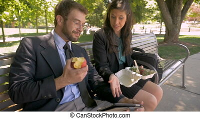 Man and woman eating healthy lunch discussing something on digital tablet