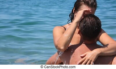 man and woman embracing and kissing in blue water of sea