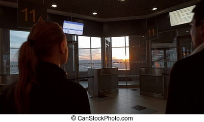 Man and woman enjoying sunset through airport window