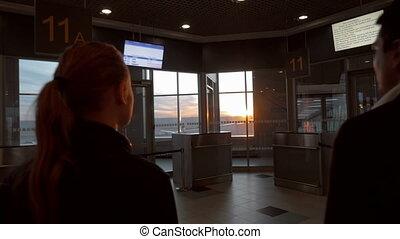 Man and woman enjoying sunset through airport window