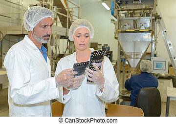 Man and woman examining packets in factory