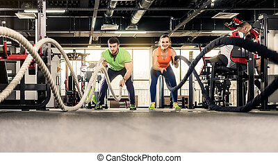 Man and woman exercising at gym