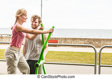 Man and woman exercising on elliptical trainer.