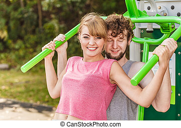 Man and woman exercising on pulldown outdoor. - Active young...
