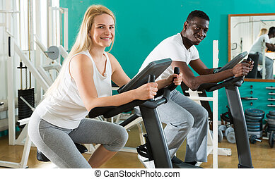 Man and woman exercising on stationary bikes
