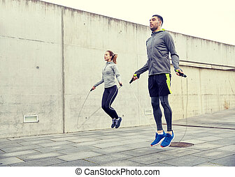 man and woman exercising with jump-rope outdoors - fitness,...