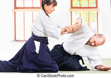Man and woman fighting at Aikido martial arts school - Man...
