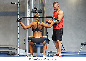 man and woman flexing muscles on gym machine - sport, ...