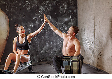 man and woman giving high-five while doing exercises with rowing machine