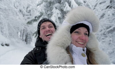 Happy couple having fun riding sleigh down snow covered mountain hill in winter forest. Man with woman or girlfriend go sledding. People on Christmas vacation.