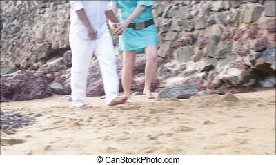 man and woman going through sand on the beach near wall