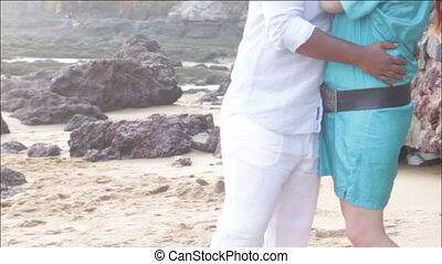 man and woman going through sand on the beach near wall