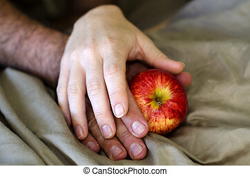 Man and Woman Hands hold Apple in Bed